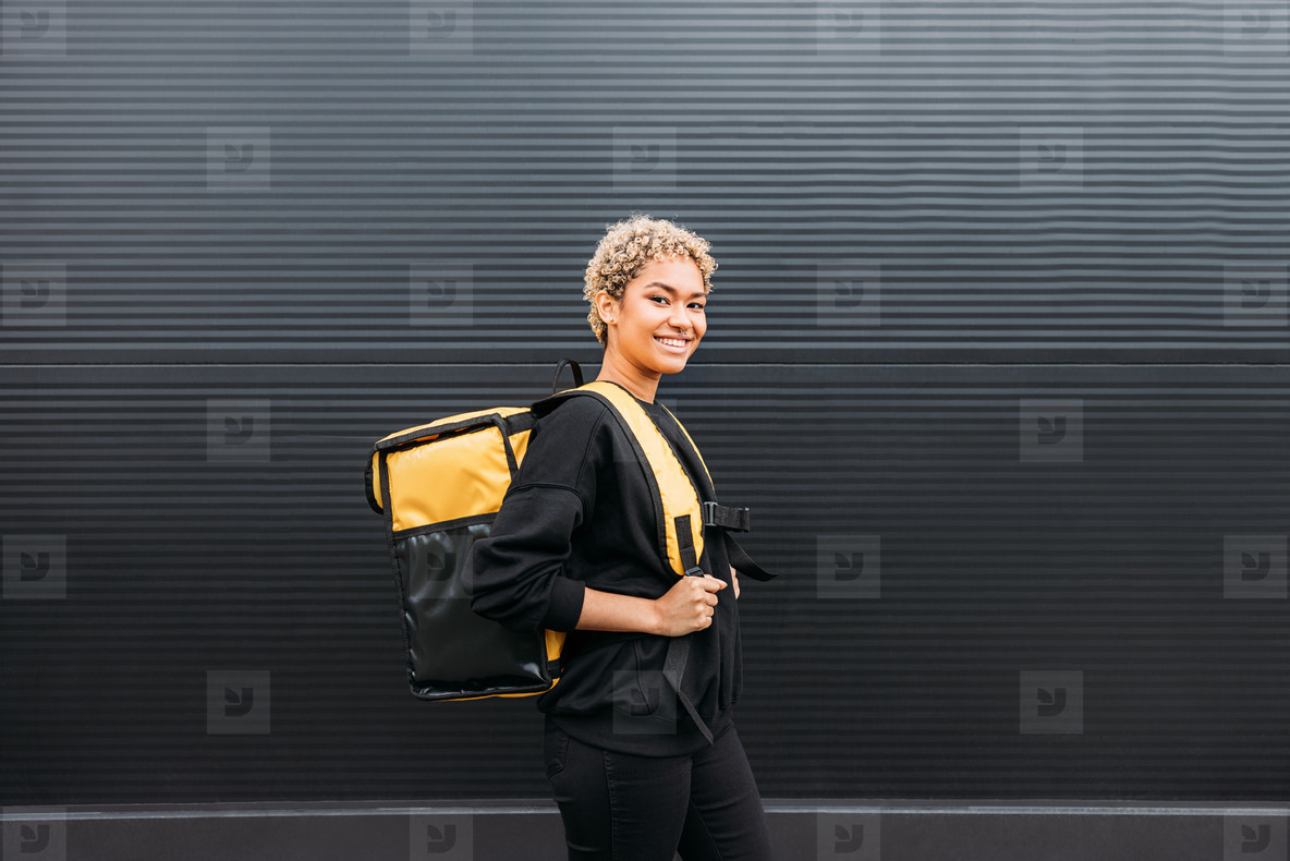 Side view of a smiling delivery girl with backpack standing at black wall outdoors
