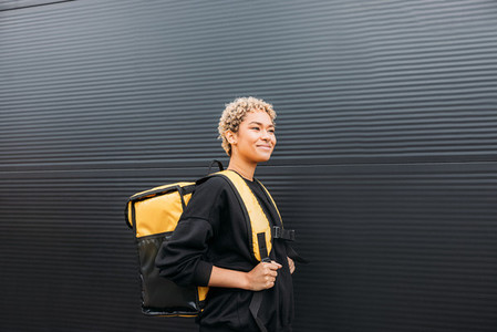 Portrait of delivery girl holding yellow thermal delivery backpack on her back and standing outdoors