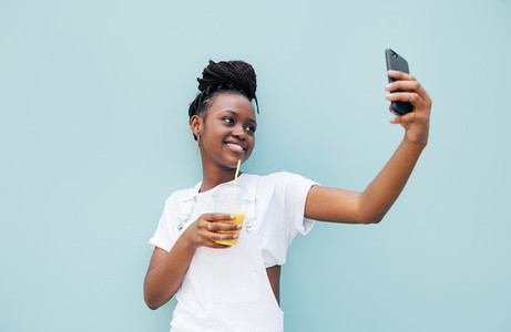Happy woman drinking juice and taking selfie near a blue wall outdoors