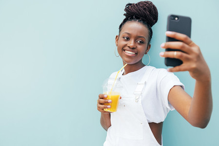 Young smiling woman holding a juice and taking a selfie while standing outdoors at blue wall