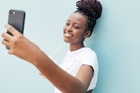 Happy woman in white clothes taking selfie near blue wall outdoors
