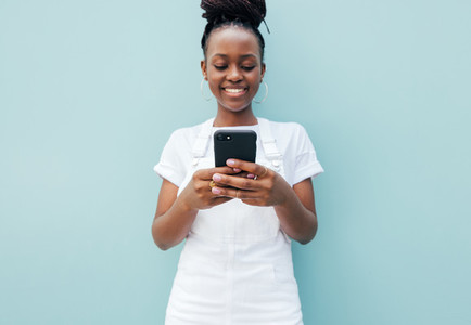 Close up of a positive young female typing on smartphone at blue wall