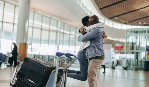 African man meeting woman arriving at airport