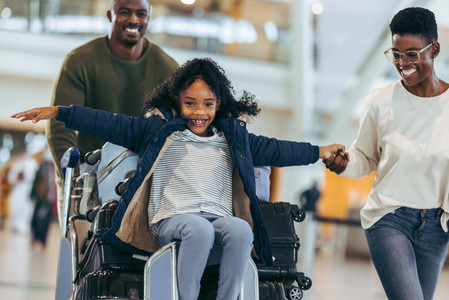 African family of three having fun at airport