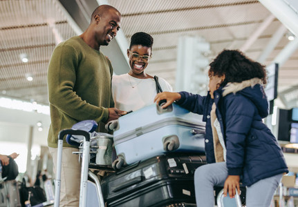 African family waiting at airport with luggage