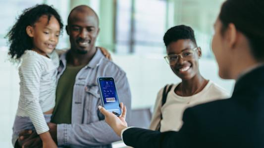 Airline attendant checking digital boarding pass of passengers