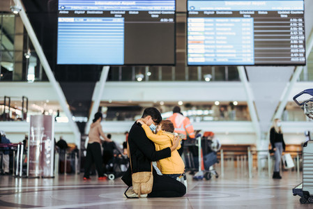 Mother hugging her son after arriving from trip