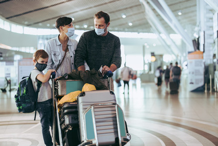 Family traveling at airport during pandemic