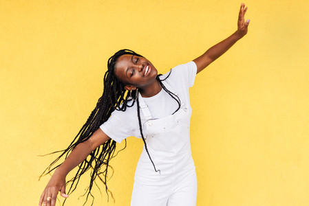 Smiling woman in white casual clothes having fun against a yellow wall outdoors