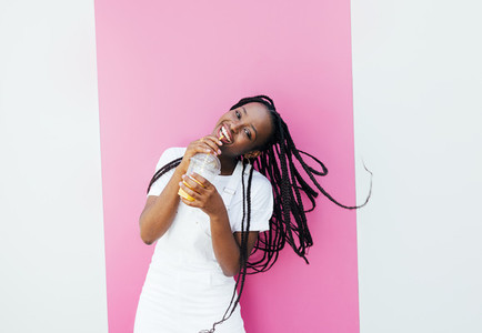 Cheerful woman with braids drinking a juice and looking at camera while standing at pink wall