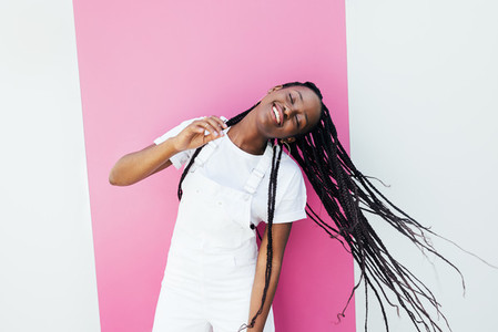 Happy female with long braided hair dancing outdoors at a wall with closed eyes