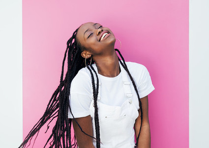 Happy woman with braids standing at pink wall outdoors with closed eyes