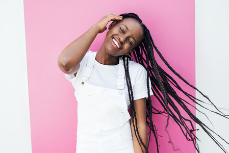 Portrait of a positive smiling woman in casuals having fun while standing at pink wall