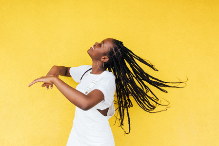 Side view of young happy woman with long braids dancing at yellow wall outdoors