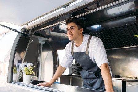 Salesman in apron leaning on a counter in food truck waiting for a clients