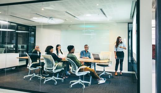 Happy businesswoman giving a financial presentation in a boardroom