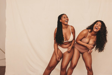 Female friends dancing cheerfully while wearing underwear