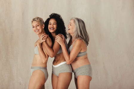 Cheerful women of different ages embracing their bodies together