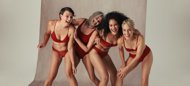 Female models of different ages having fun in red swimwear