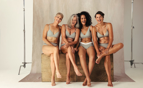 Four confident women of different ages in their natural bodies