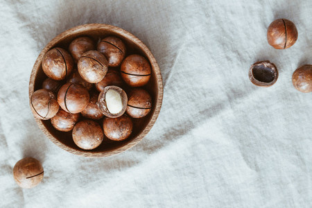 Top view of macadamia nuts in a wooden bowl on a table