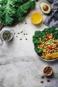 Food frame background with salad  greens and seeds on a grey table