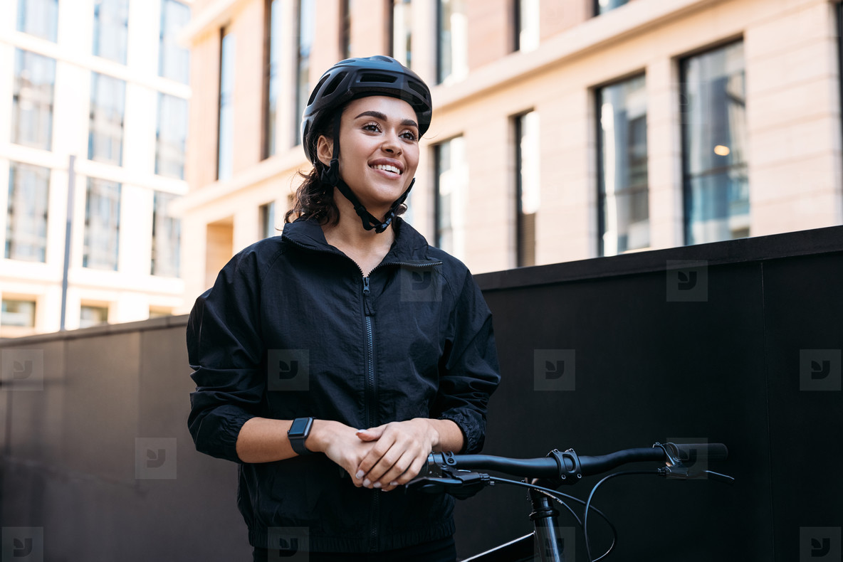 Portrait of a young female standing with a bicycle  Delivery woman taking a break during a working day