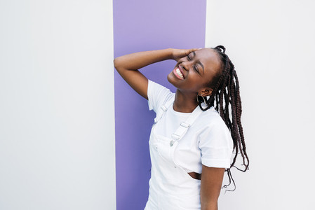 Happy woman with closed eyes wearing white clothes leaning on white wall with purple stripe