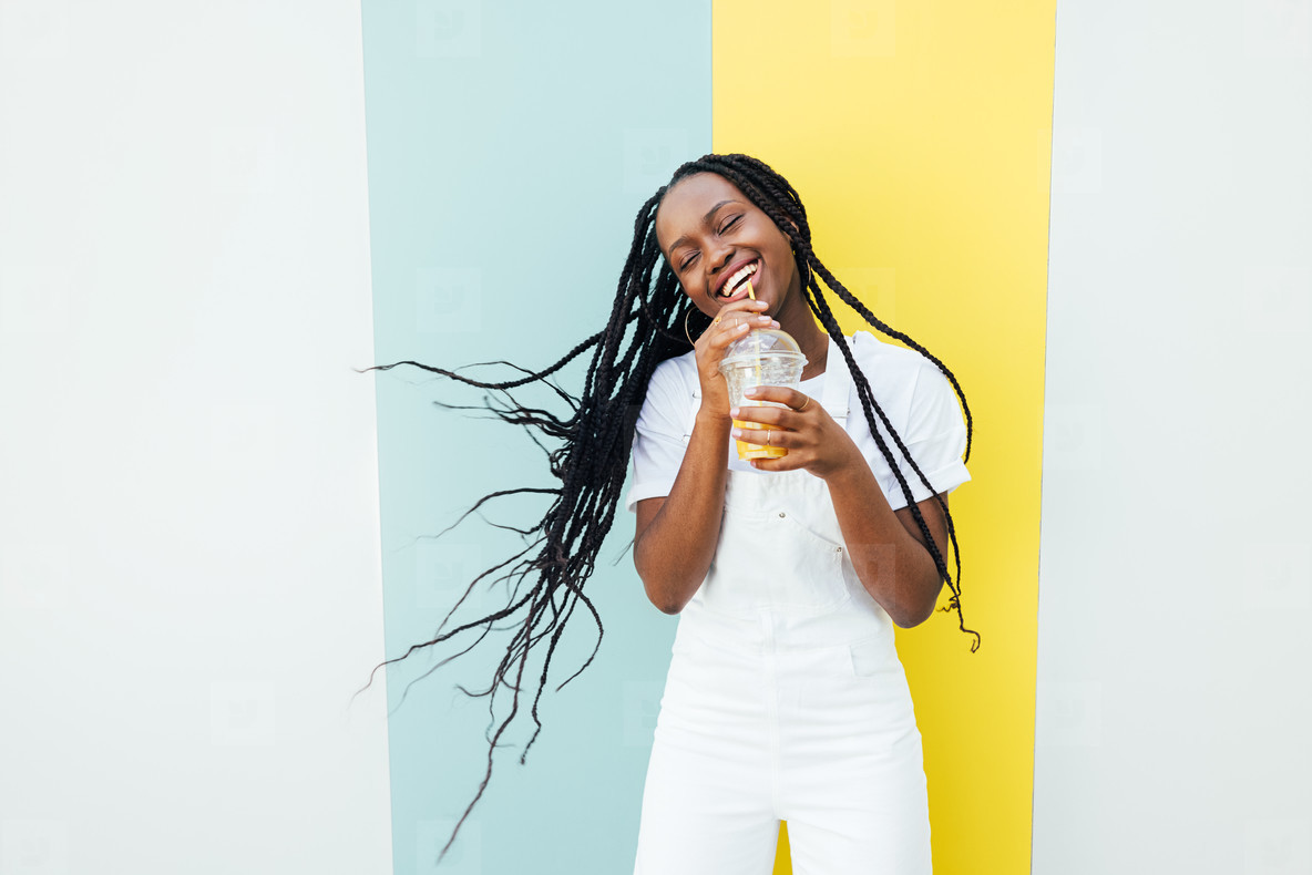 Happy woman with long braided hair having fun while drinking orange juice at a wall with blue and yellow stripes
