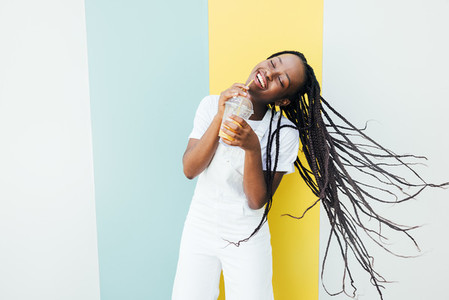 Cheerful woman with closed eyes drinking orange juice while dancing at a wall with blue and yellow stripes