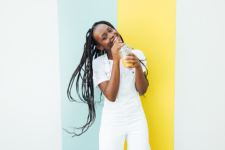 Playful woman in white overall drinking juice and looking at camera while standing at wall outdoors