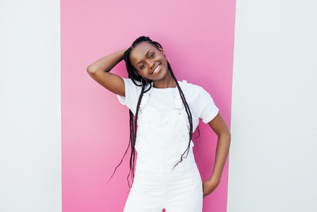 Portrait of a young cheerful girl wearing a white overall standing at wall with pink stripe