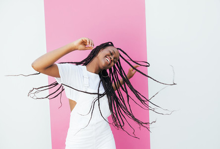Playful woman with long braided hair dancing at a white wall with pink stripe