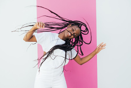 Young happy woman with long hair having fun against white wall with pink stripe