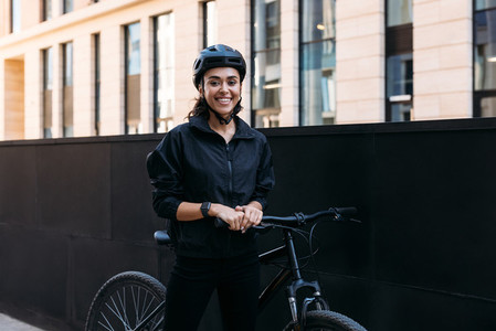 Beautiful smiling woman in black cycling helmet looking at camera while standing in the city