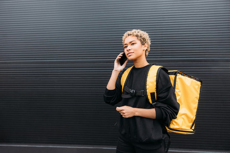 Portrait of a delivery girl with yellow thermal backpack on her back talking on smartphone at a black wall