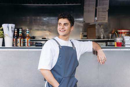 Portrait of a young waiter standing at a food truck and looking away