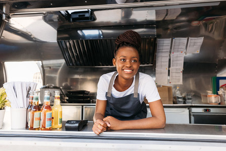 Portrait of young small business owner standing in her food truck waiting for clients