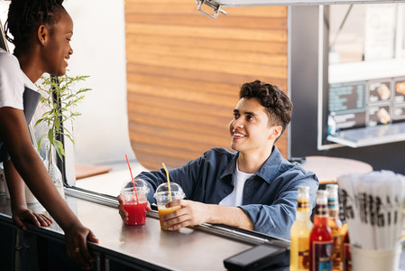 Young man holding juice on a counter of food truck looking at saleswoman