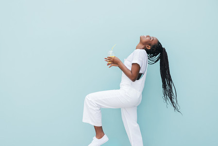 Side view of woman in white clothes having fun against blue wall  Young female holding a juice enjoying good mood