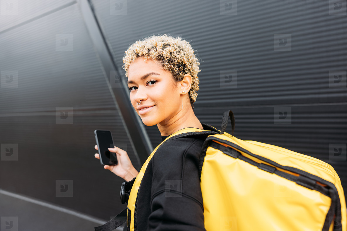 Portrait of smiling delivery woman with bag standing on a sidewalk and holding smartphone