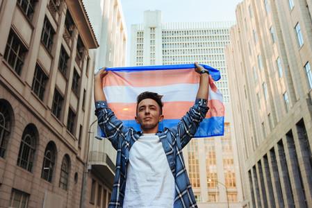 Transman raising the transgender flag in the city