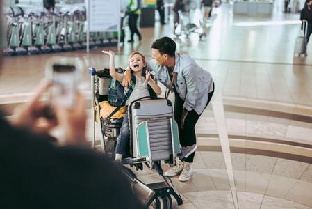 Family at airport taking photos and having fun