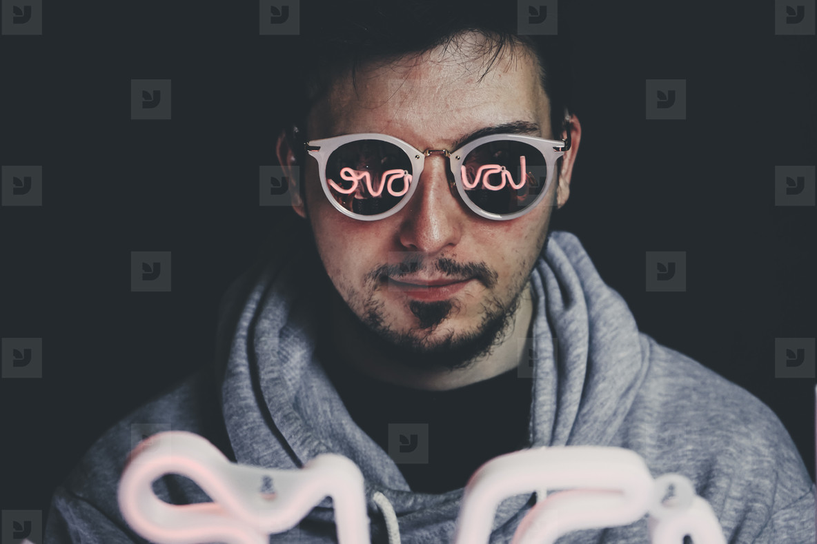 Young man holding a neon light in front of him