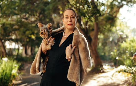 Luxurious woman looking at the camera while holding her puppy