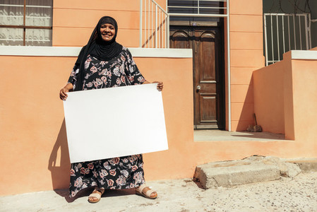 Smiling Muslim woman holding a blank placard outside her home
