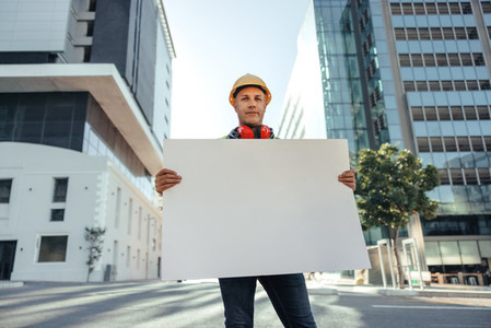 Blue collar worker holding a blank placard in the city
