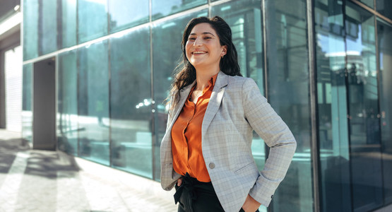 Businesswoman laughing cheerfully outside her workplace