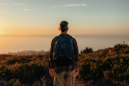 Unrecognisable backpacker looking at the view on a hilltop