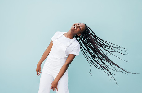Happy woman with long braided hair having fun against a blue wall outdoors
